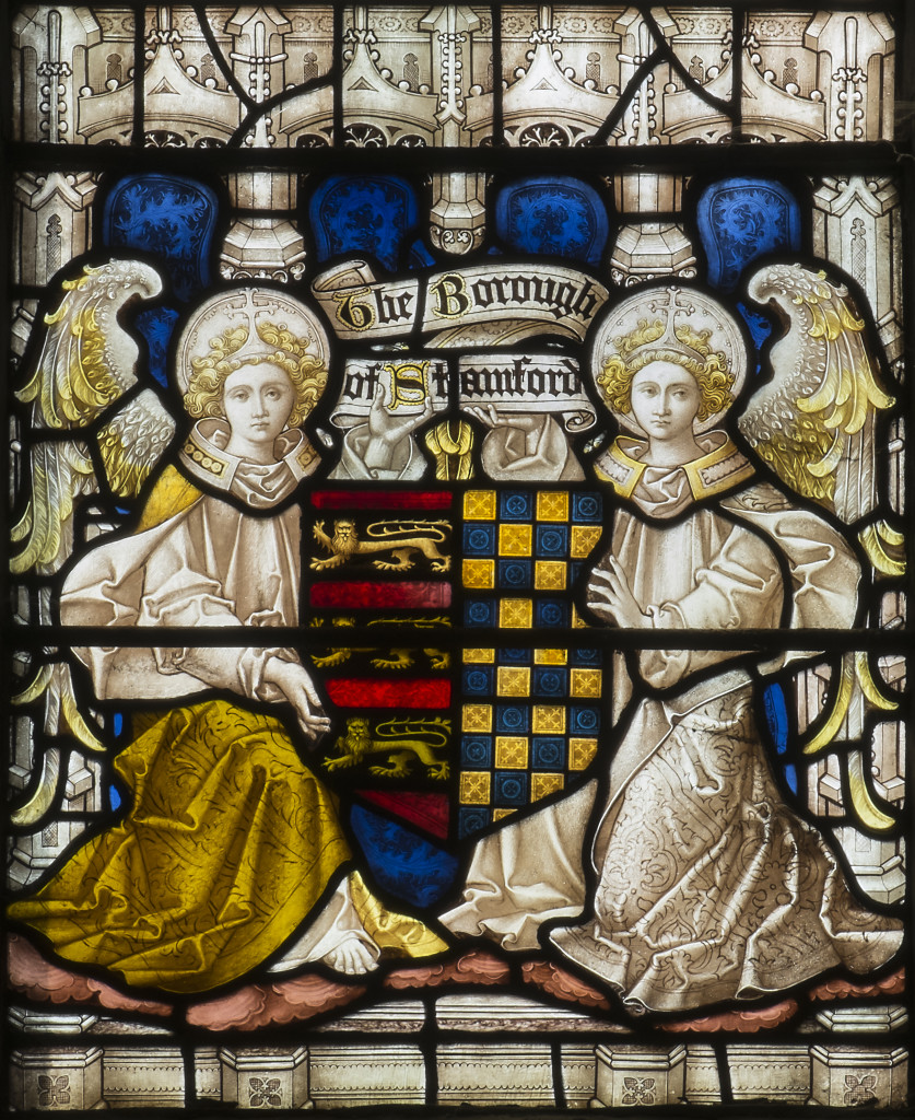 Detail of the west window by Clayton and Bell, showing two angels holding the coat of arms of the Borough of Stamford